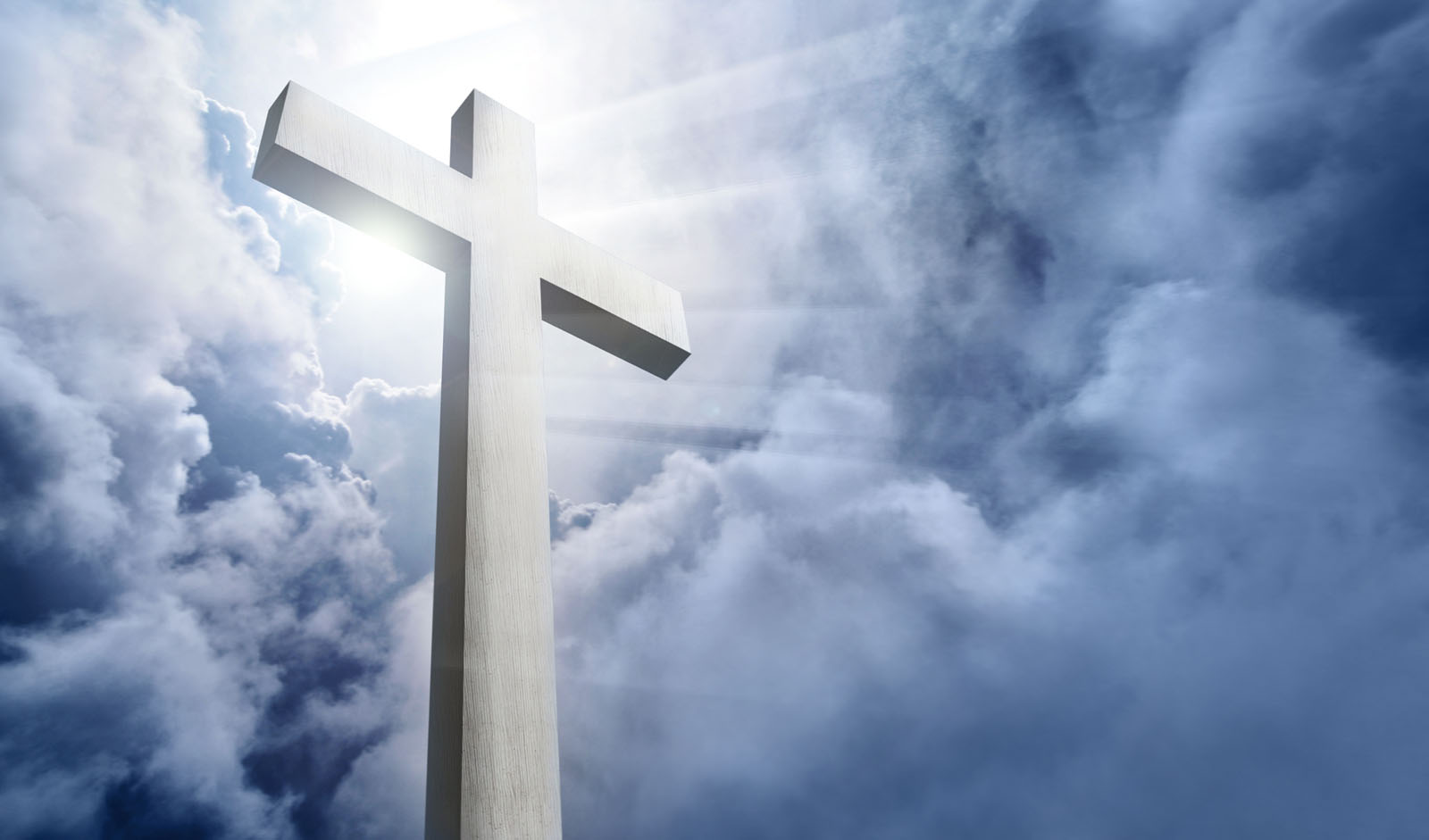 White wooden cross (render) standing in front of a cloudy sky with sunbeams shining forward.